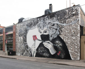 mural on side of building woman in mask with red rose